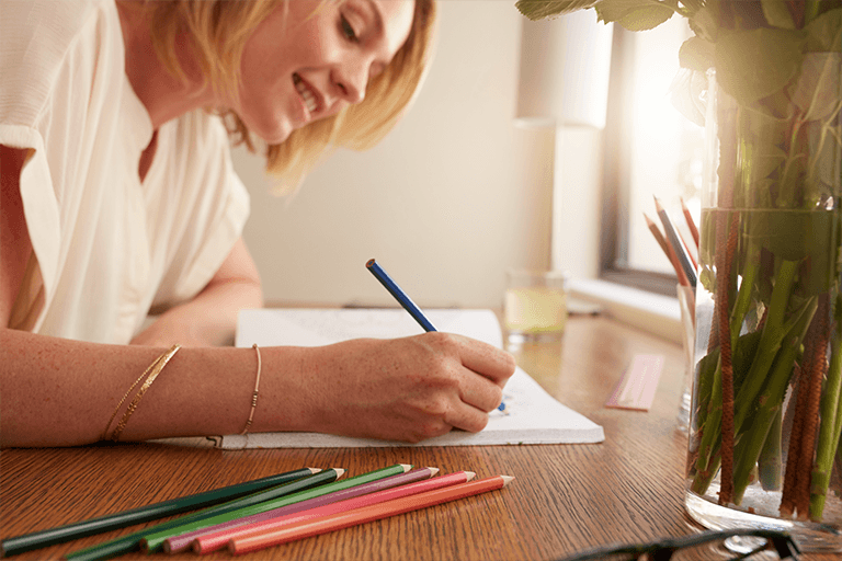 woman writing in a notebook with colored pencils