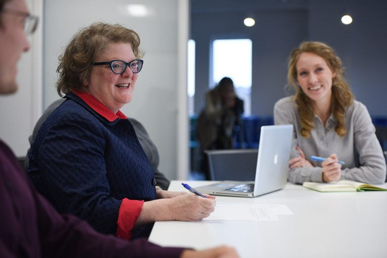 Two women at a conference table smiling.