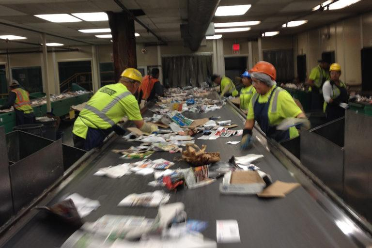 Workers with green vests and hard hats at recycling conveyer belt sorting recycling.
