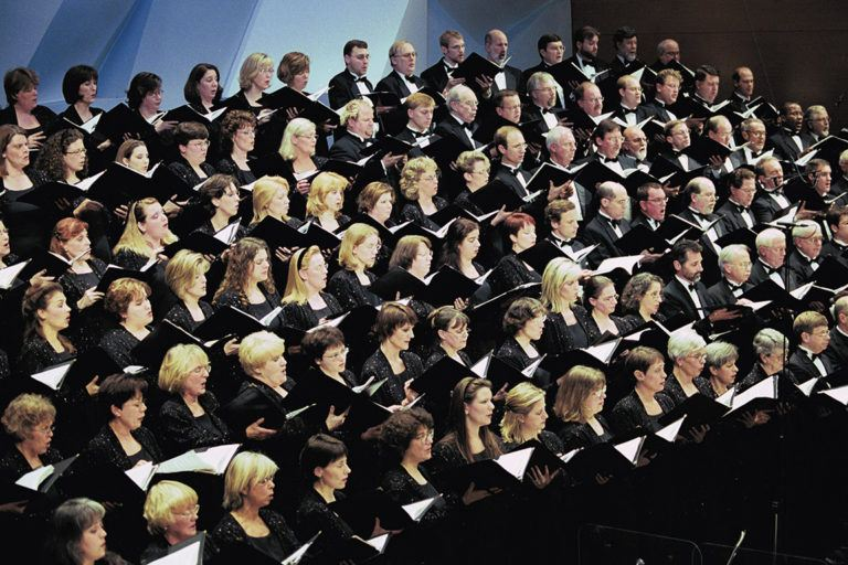 Minnesota Chorale singing, all dressed in black with songbooks open.