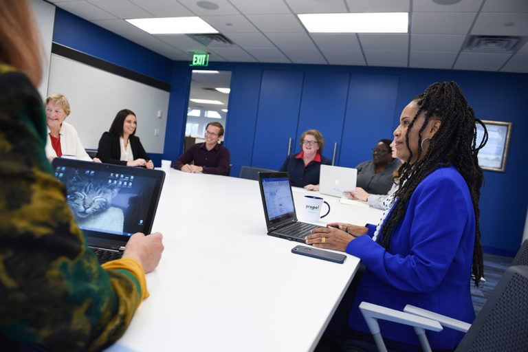Group of people with computers sitting at a conference table.