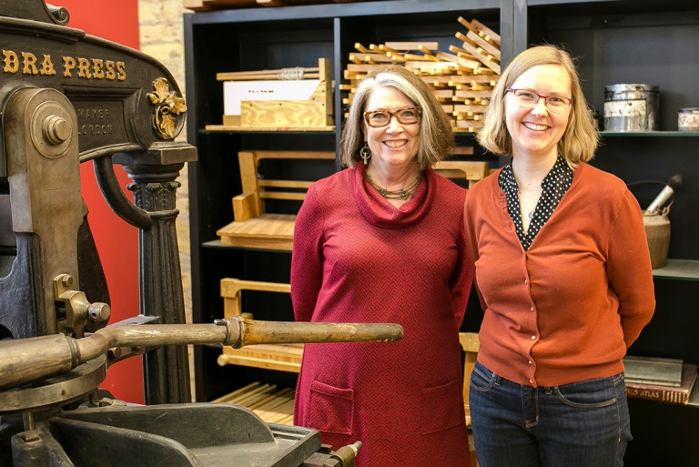 KC Foley and Amanda Kaler standing in front of an old book press at Minnesota Center for Book Arts.