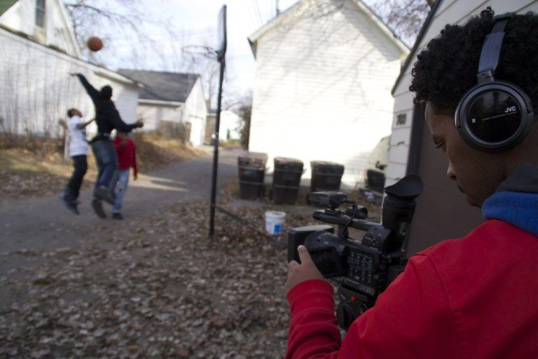 Young man filming three other young men playing basketball in an alley, part of FilmNorth MN's programming.