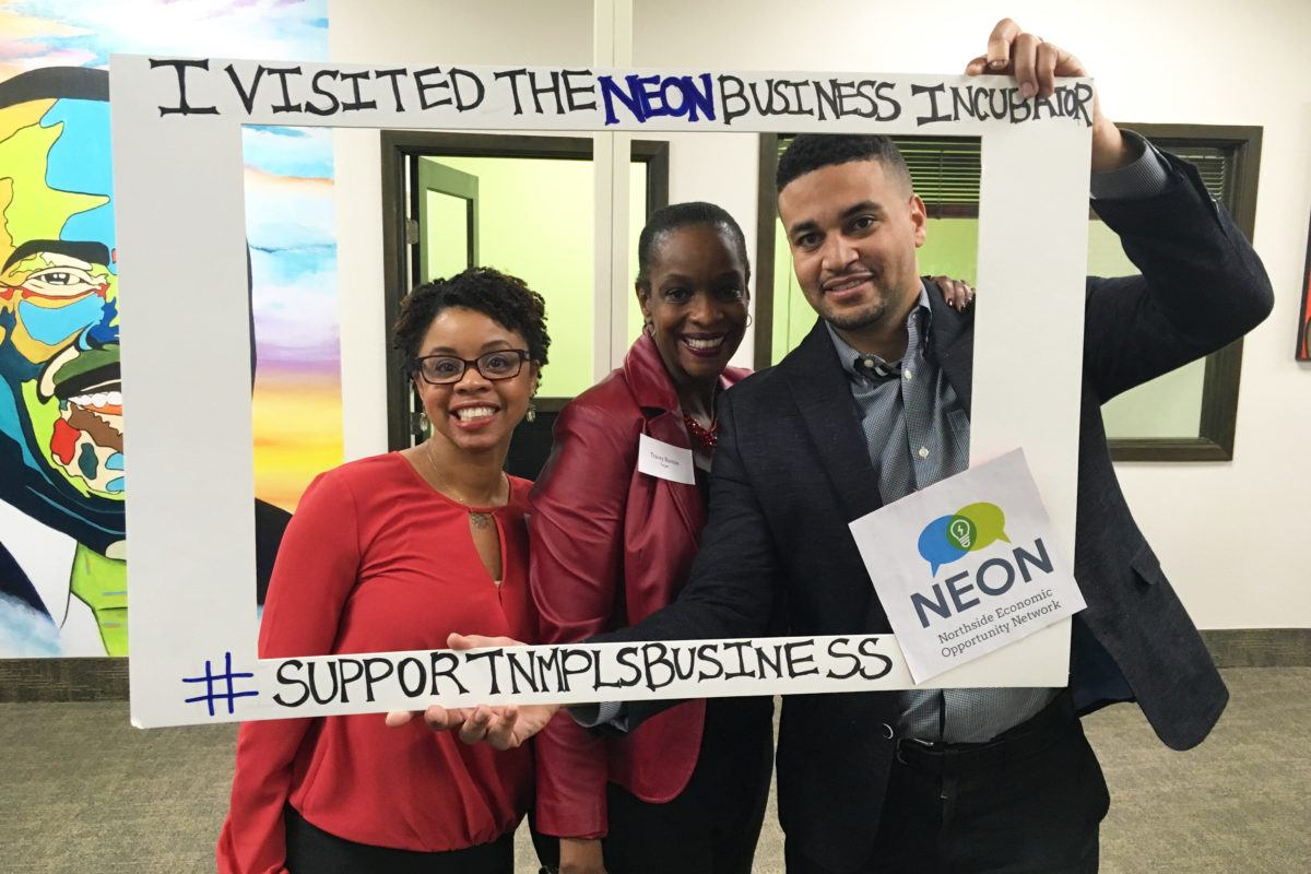 Three people holding sign for NEON's incubator fundraising campaign.
