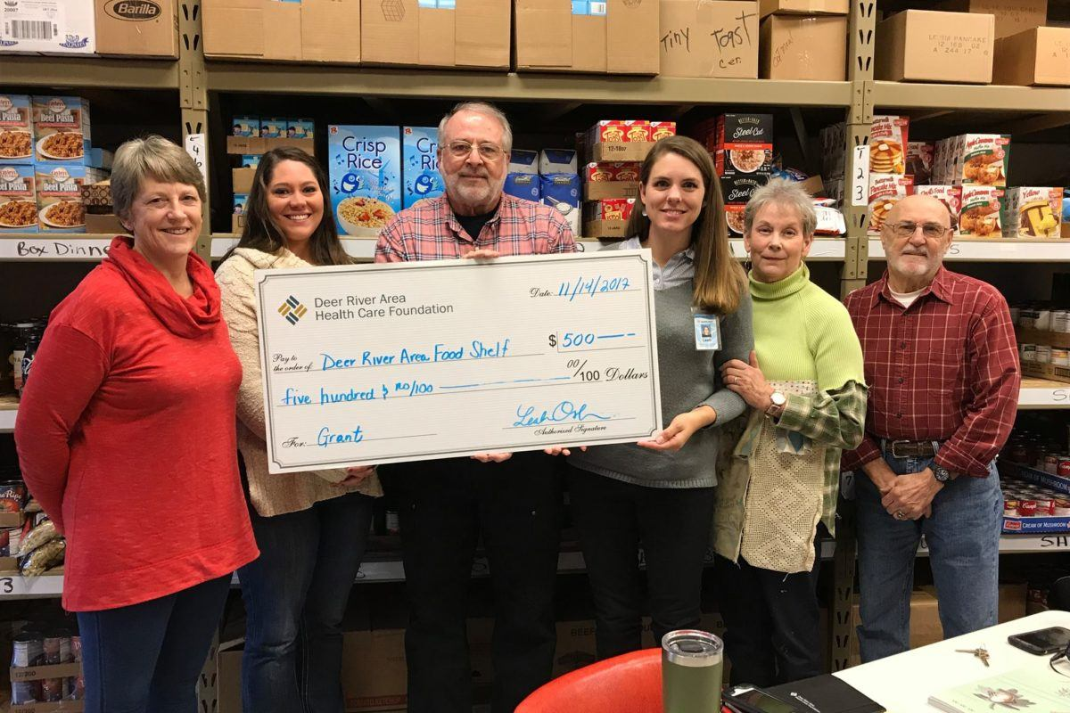 Six people holding a check: Deer River Area Health Care Foundation making a donation to the local food shelf.