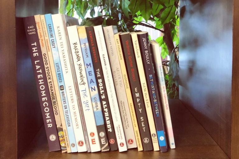 Books stacked in a cubby, all published by Coffee House Press.