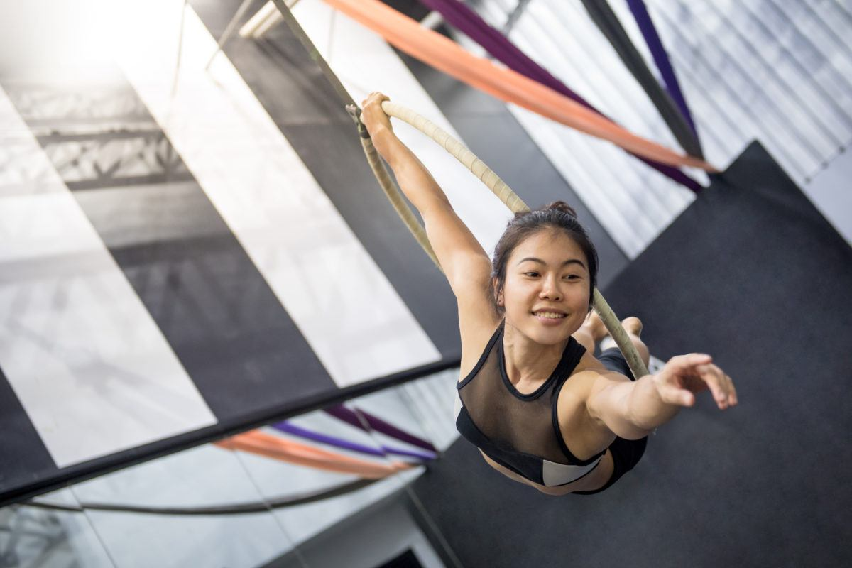 Young acrobatic woman performing on aerial hoops; while your audit might seem like a hoop to jump through, you can actually use it to audaciously tell your financial story.