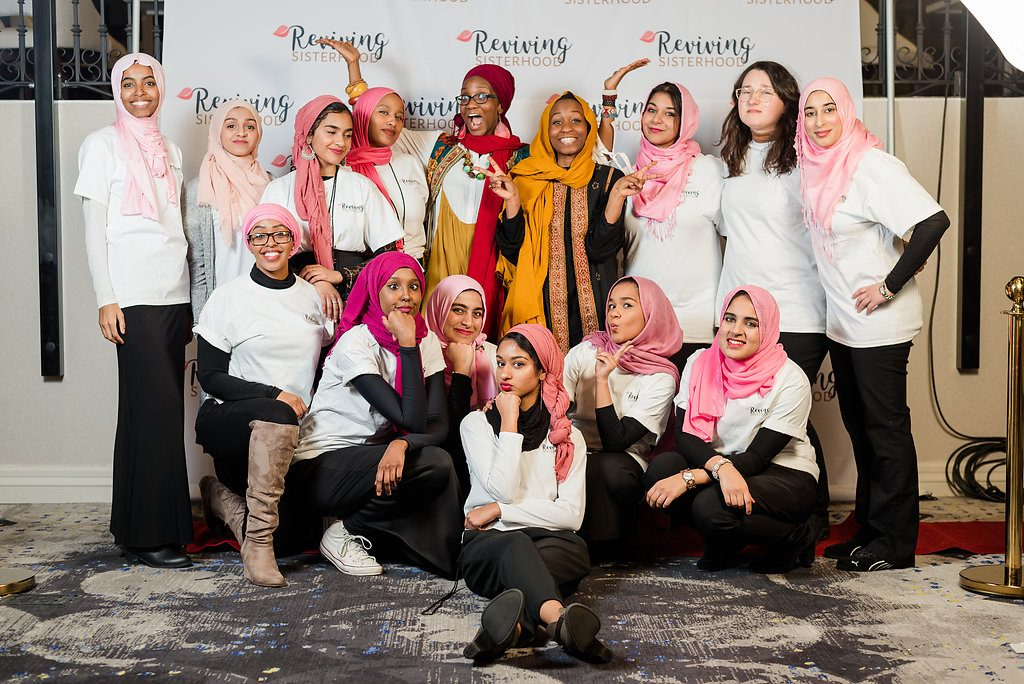 Fun photo of Muslim women posting at Reviving the Islamic Sisterhood for Empowerment's conference.