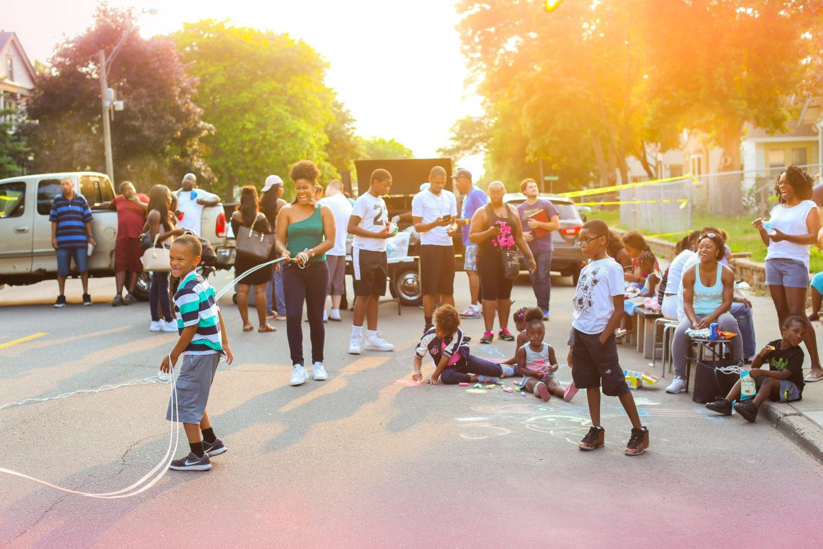 People on the street at golden hour, kids jumping rope, coloring with chalk at Minnesota Harvest Initiative/National Night Out at H White Men's Room in North Mpls. Photo by Katherin Louise Harris of The Jadeite Shutter.