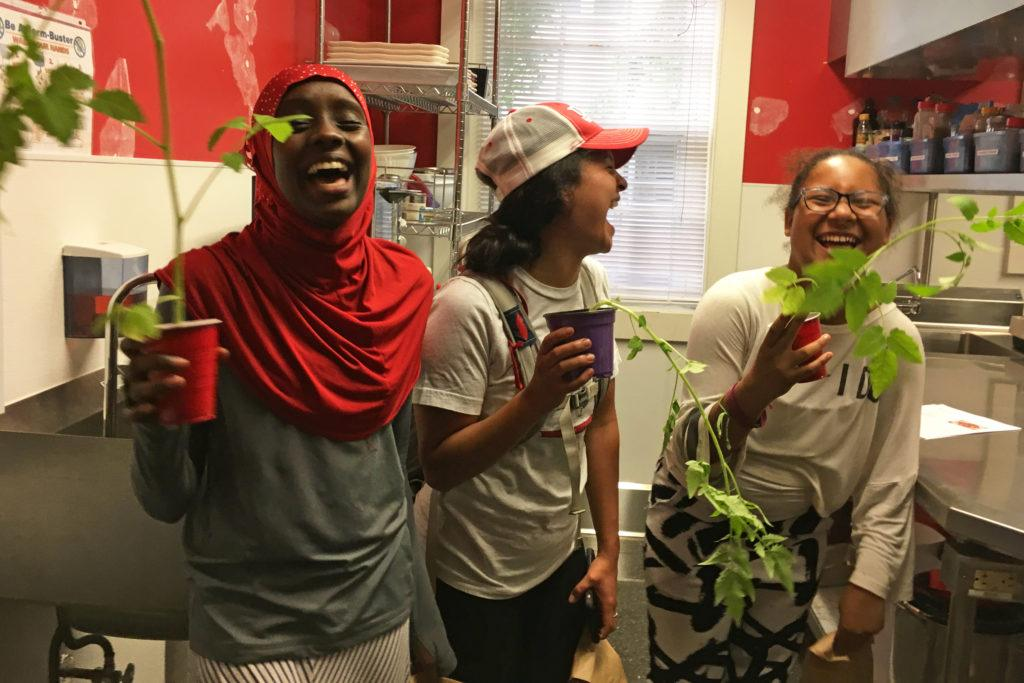 Three young women laughing holding plants.