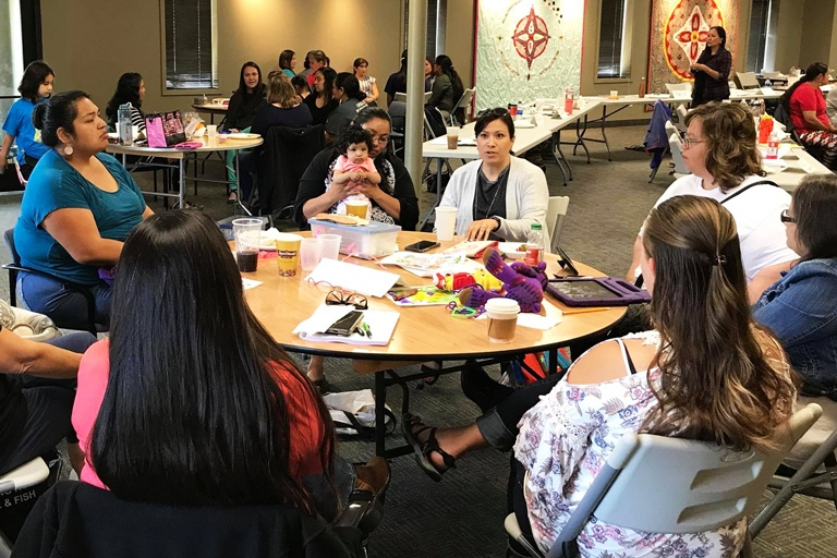 Natalie Nicholson at a table talking with other Native women
