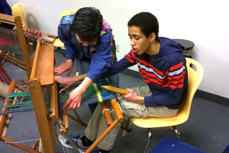 Student working with teaching artist Chiaki O'Brien to create a weaving using the Saori method at a school for transition-aged students in White Bear Lake (May 2018)