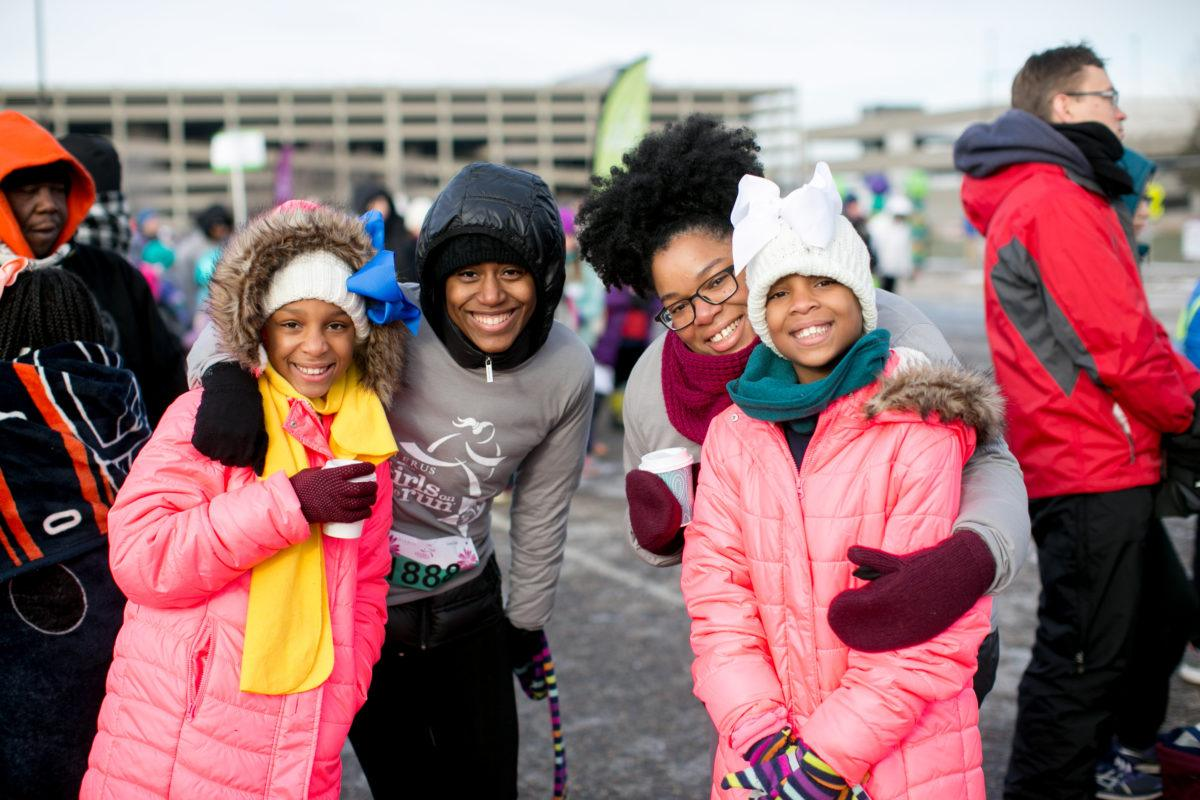 Two girls with two women, smiling and bundled up after a winter running race.