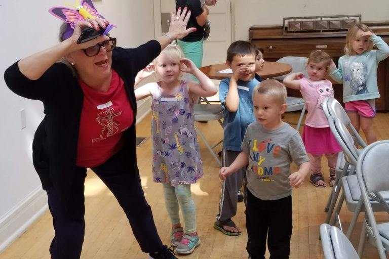 Woman leading group of children in theater exercises