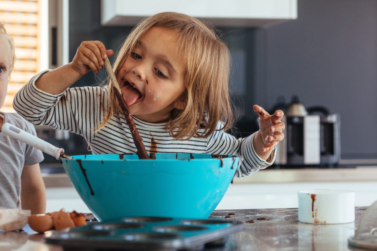 Little girl licking spoon while mixing batter for baking in kitchen and her brother standing by. Cute little children making batter for baking.