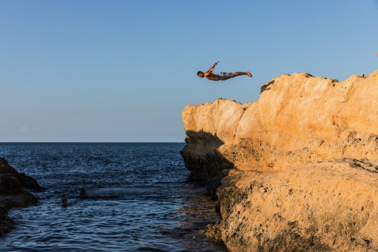 Young man jumping from rock to sea. Cliff Jumping into the Ocean at Sunset