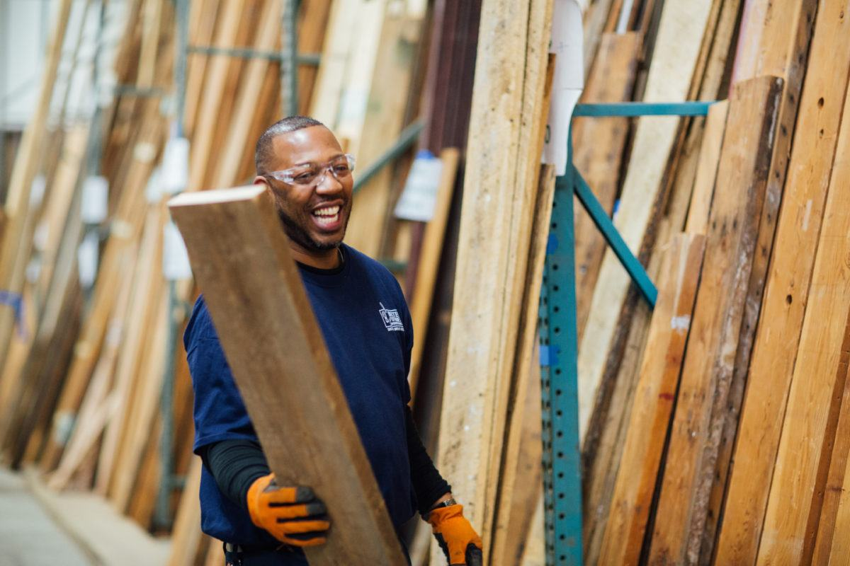 Man stacking wood at Better Futures warehouse