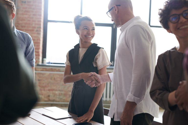 Woman and Man shaking hands in a meeting