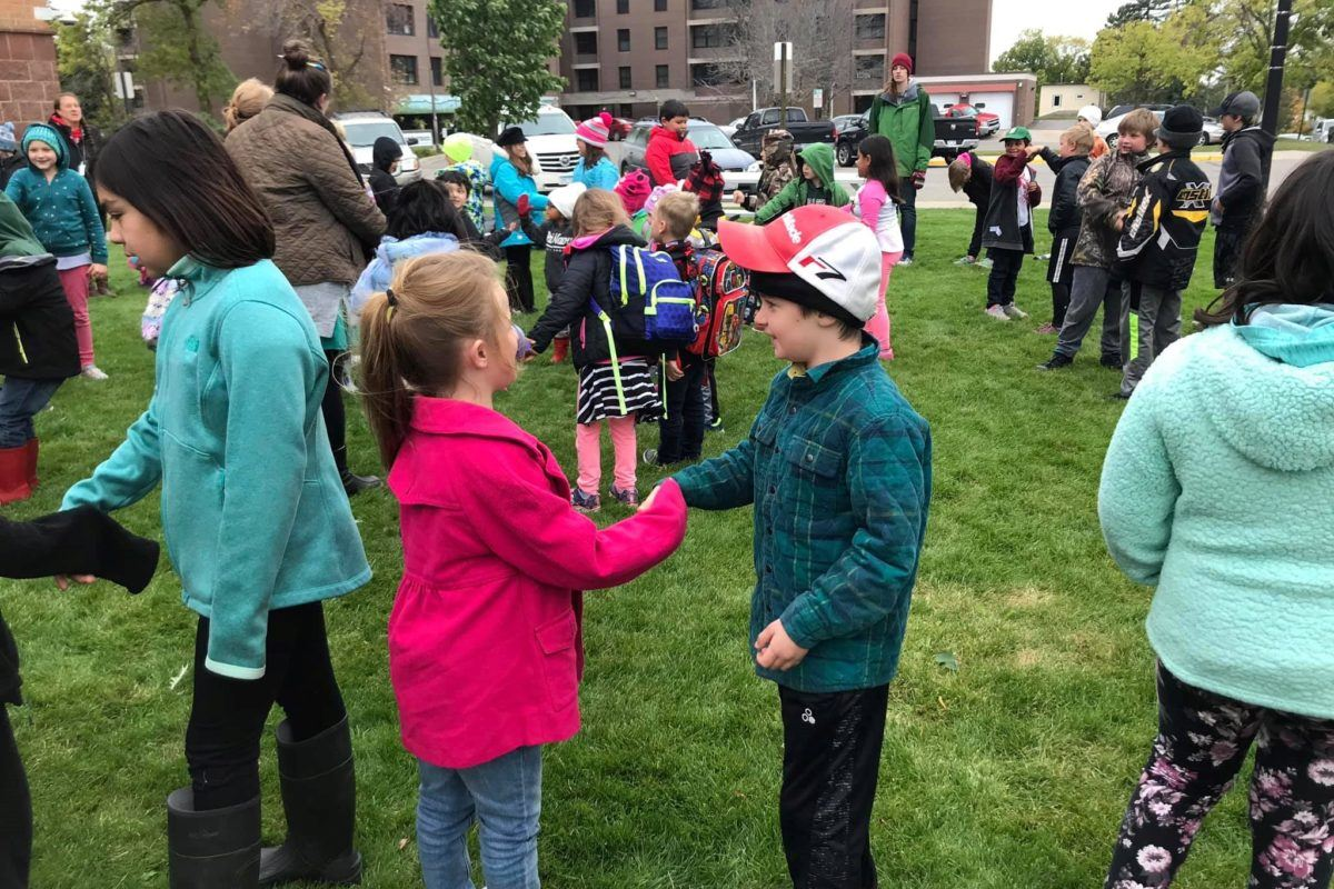 Young kids in pairs on grassy lawn shaking hands