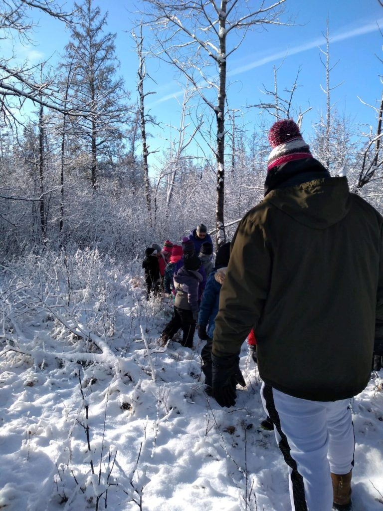 Students walking through snow to woods