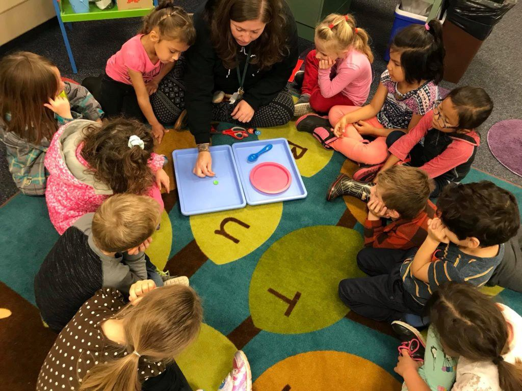 Kids sitting in circle on floor watching teacher sort objects