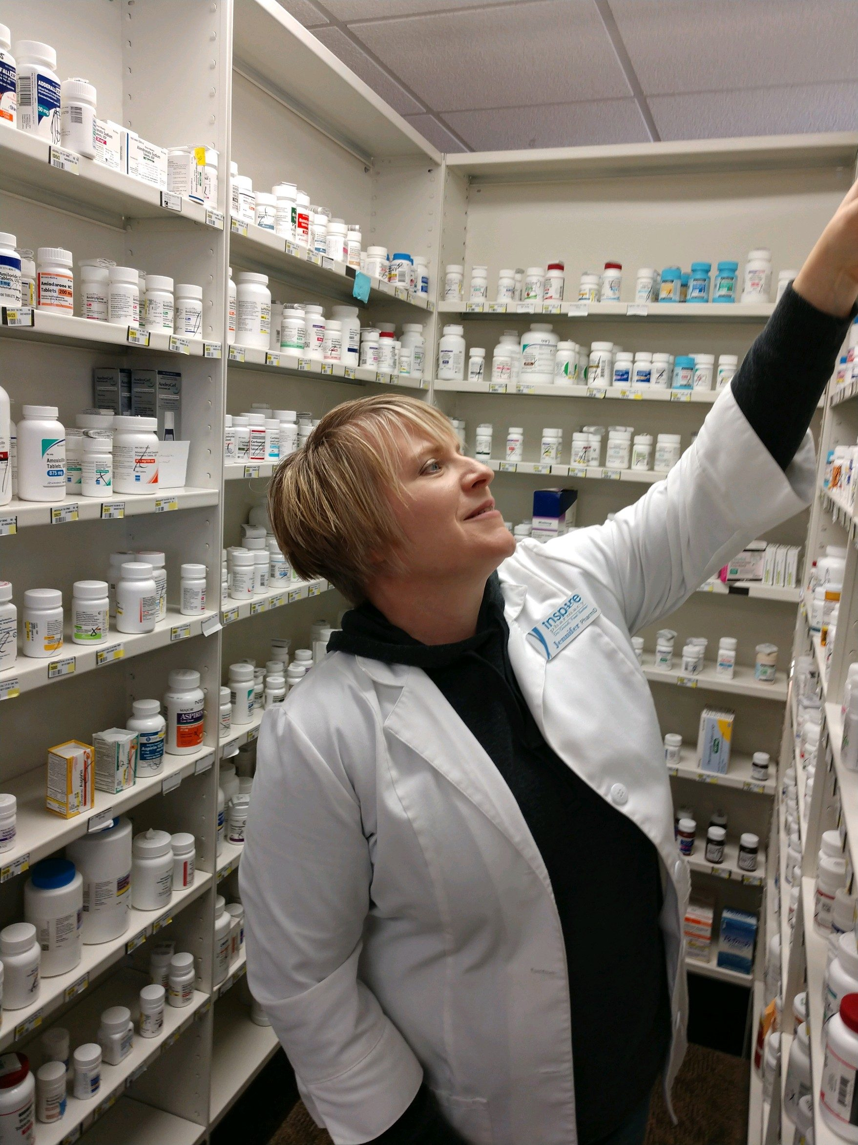 Woman reaching up to get medication bottle in a pharmacy