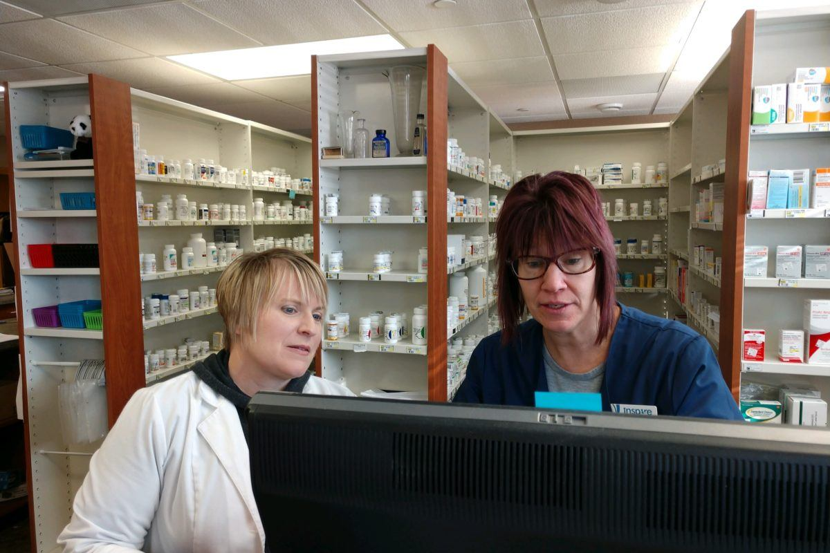 Two women at a pharmacy looking at computer screen
