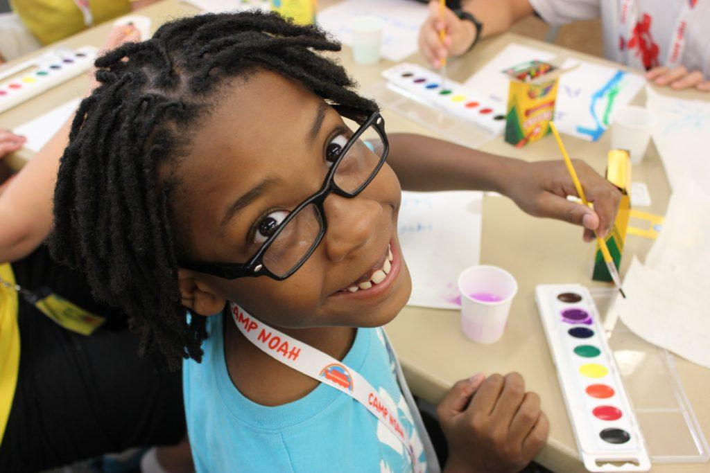 A girl smiling up at the camera while painting