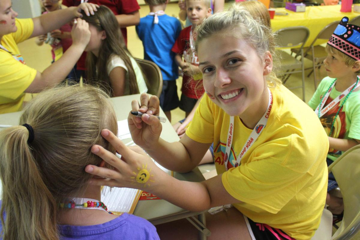 young woman smiling at camera while painting the face of a little girl