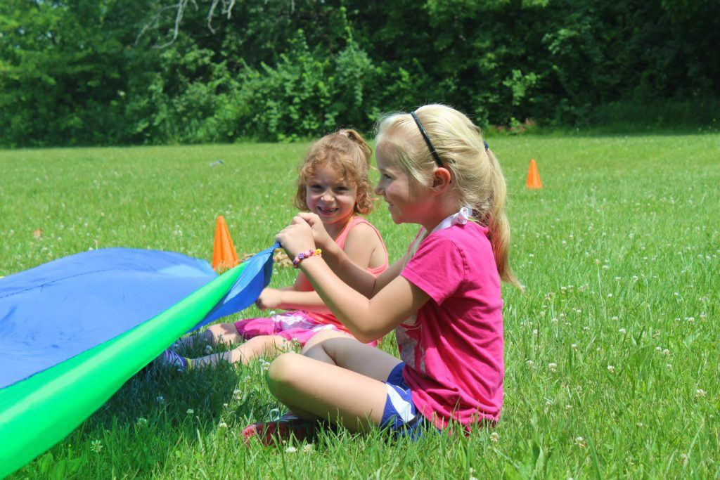 Two little girls sitting in a grassy field holding edges of a parachute