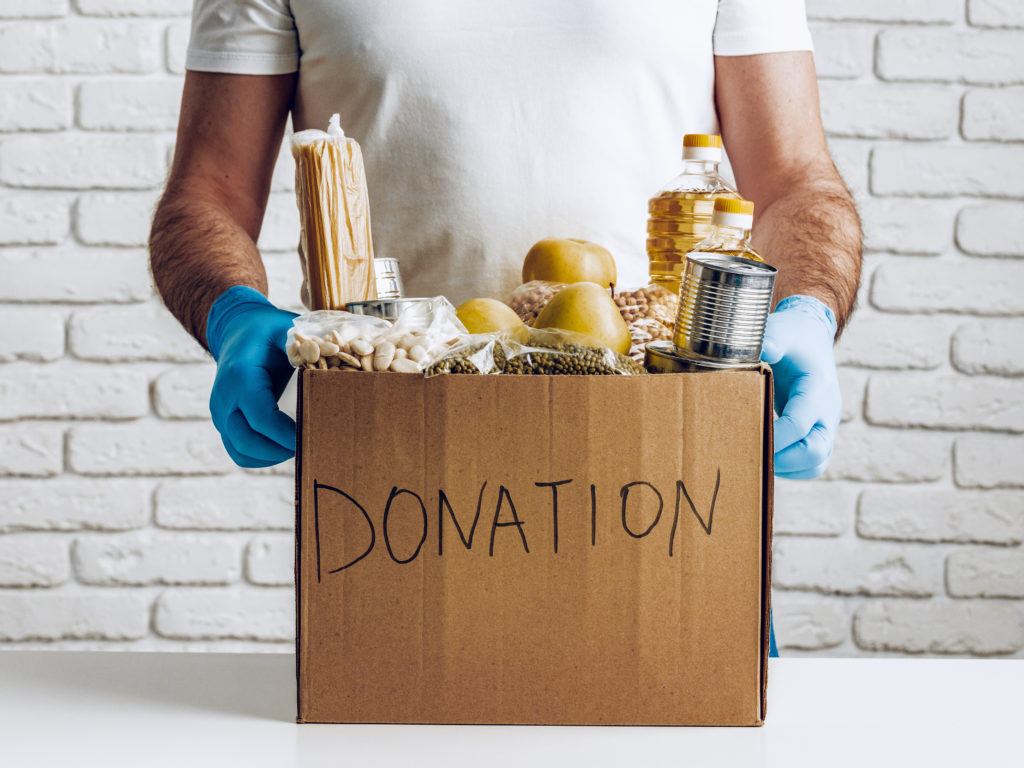 "A person wearing blue latex gloves holding a cardboard ""donation"" box filled with food items."