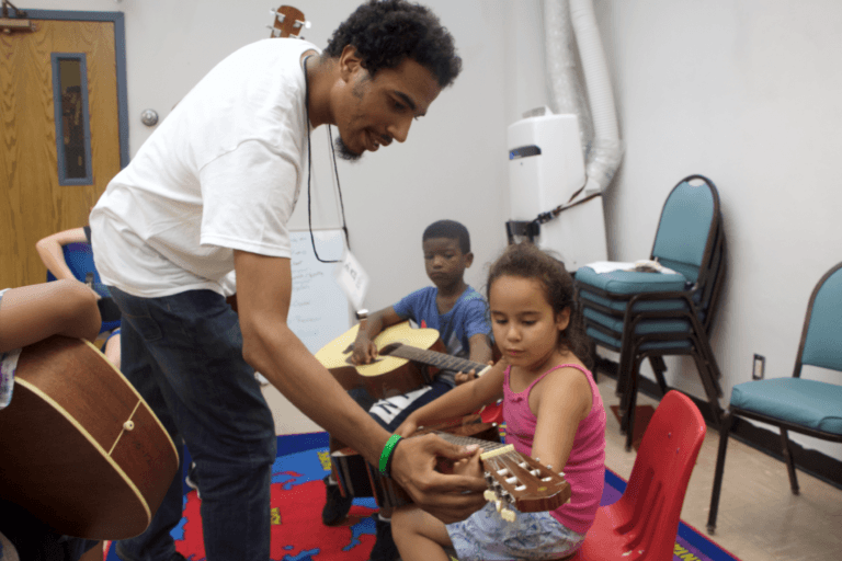 Andre Bronson, violin & early childhood instructor at Hopewell, teaches a student a chord on guitar.