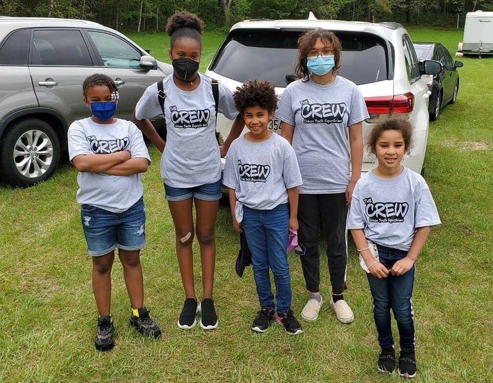 Youth from the crew pose with matching t-shirts