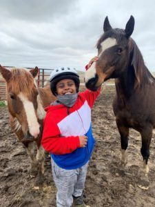 a black youth pets a horse and wears a big smile